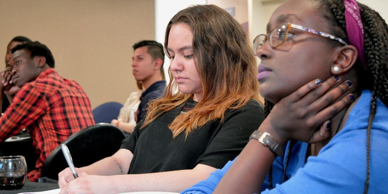 NCUK 여러 나라의 학생들이 회의실에서 연설을 듣습니다.